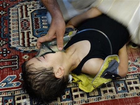 A boy, affected by what activists say is nerve gas, breathes through an oxygen mask in the Damascus suburb of Saqba