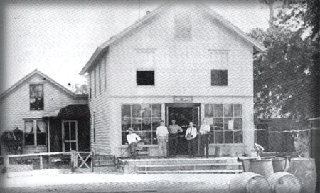 General Country Store, 1911.  Pictured are left to right, Buren Baldwin, Horace Bennett, Unknown, Ebinback, and Mr. Robinson, father of Joe Robinson.  Street in front is Halifax Ave as it is called today. Used to be old Dixie Highway.  The Post Office stands here today.